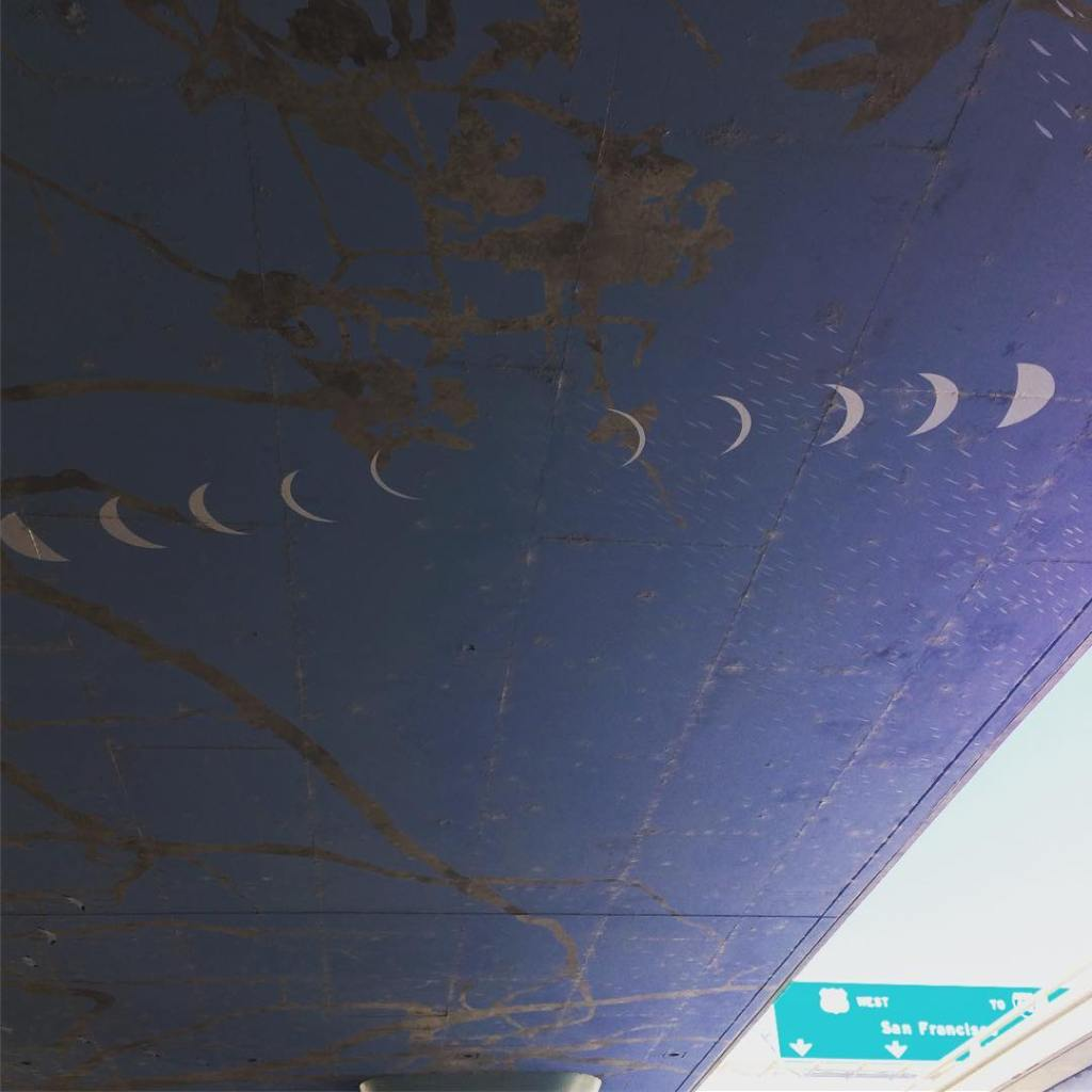 Photo of white moon phases painted on blue on the underside of a freeway
