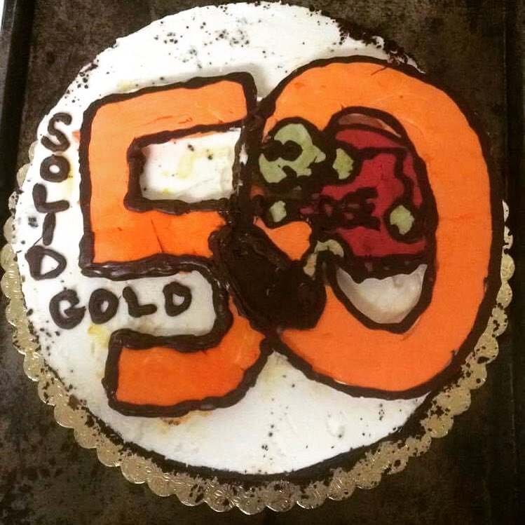 Aerial view of a cake decorated in white buttercream, the words Solid Gold written in brown icing, and a large orange number 50 with a turtle wearing a red shirt