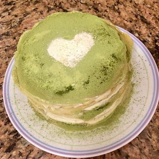 Photo of a tall stacked crepe dessert dusted with green matcha powder and decorated with a white powdered sugar heart, set on a purpled-ringed ceramic plate atop a marble counter
