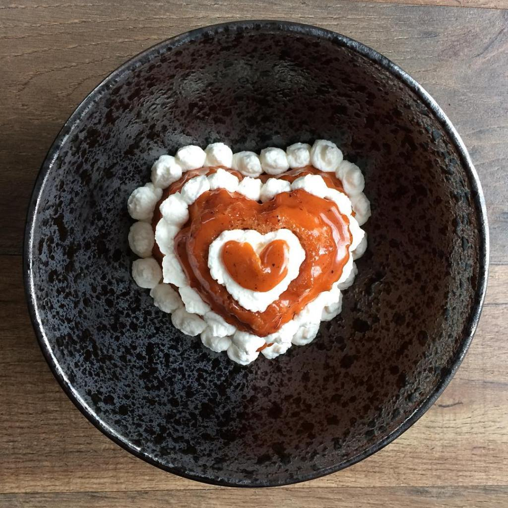 Aerial photo of a red and white heart-shaped dessert in a grey ceramic bowl