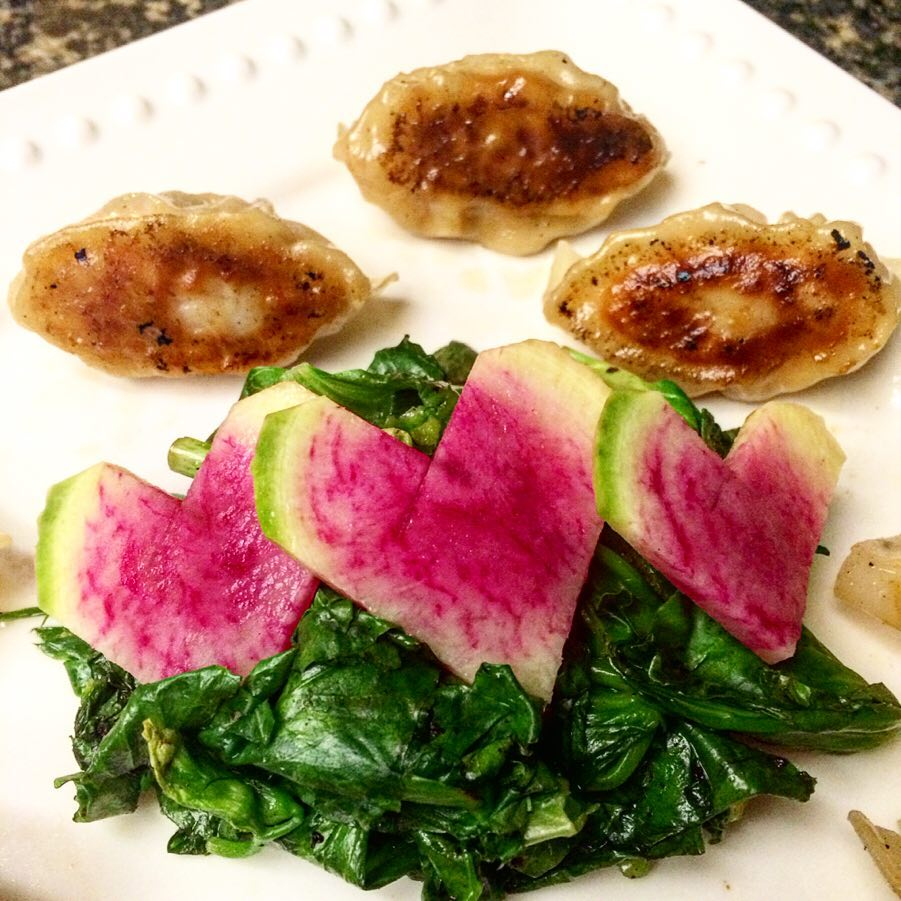 Plate of 3 pan-fried dumplings and sauteed greens topped with 3 watermelon radishes cut into heart shapes