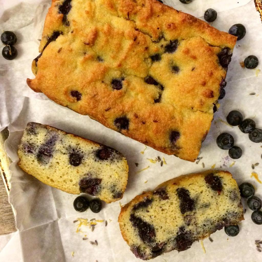 Photo of a blueberry loaf with two slices set next to it and blueberries sprinkled around